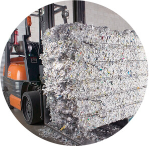 Image of forklift truck carrying bale of shredded paper